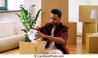 indian man packing boxes and moving to new home - moving,...