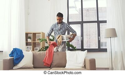 indian man picking clothes for laundry at home - housework,...