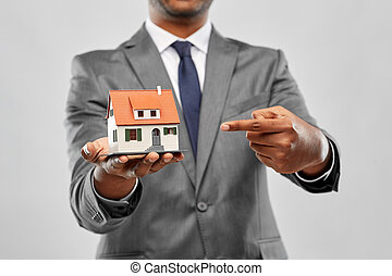 indian man realtor with house model and folder - real estate...