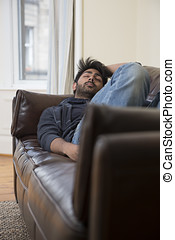 Indian man sleeping on couch at home.