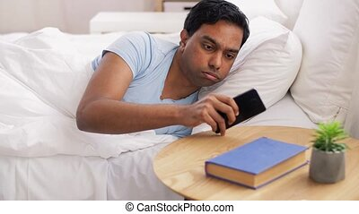 people, bedtime and rest concept - sleepy indian man in bed suddenly awaking and looking at smartphone lying on table at home