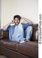 Indian Man using his phone at home.