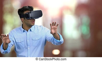 Indian man wearing virtual reality goggles. Scared man wearing vr headset. Blurred bokeh background.