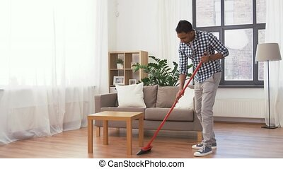 indian man with broom cleaning floor at home