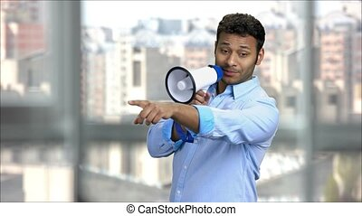 Indian man with megaphone giving instructions. Office manager giving commands.