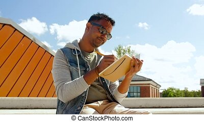 indian man with notebook or sketchbook on roof top -...