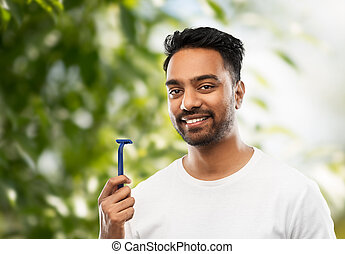 indian man with razor over natural background