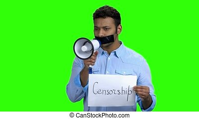 Indian man with taped mouth holding megaphone. Taped mouth...