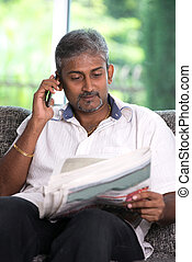 indian mature male on phone conversation while reading newspaper