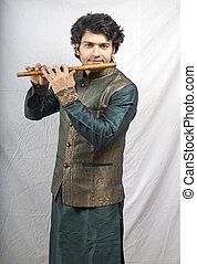 indian model in green kurta playing flute