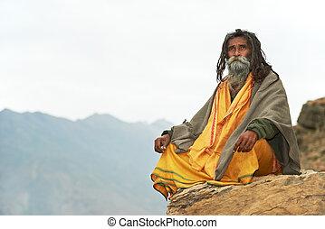 Indian old monk sadhu in saffron color clothing