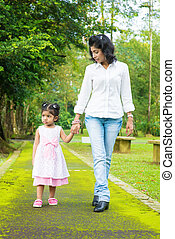 Indian mother and daughter walking outdoor.