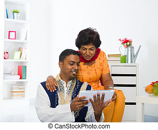 indian mother and son enjoying surfing with tablet in the livingroom