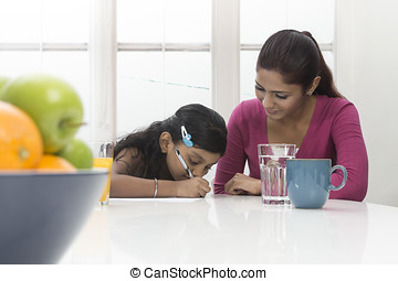 Indian mum helping child with homework - Indian Woman...