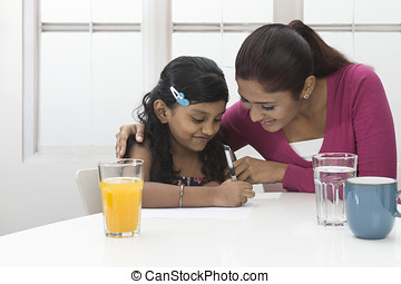 Indian mum helping young girl with homework at home