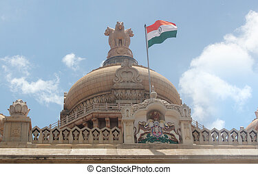 Indian national flag in tri color (orange, white & green) with ashoka chakra on vidhana soudha legislative building at bangalore, karnataka with dome &  national emblem of india(lions) in background