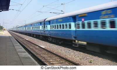 Indian passenger train passes by a countryside near...