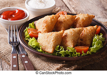 samosa delicious pastry on a plate with tomatoes and lettuce...