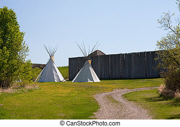A small group of tepees in a meadow surrounded by forest. Tepees were traditional housing for Native Americans in Great Plains and other Western states.
