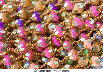 Indian traditional culture stuff from colourful beads pink violiet orange gold for holy religious ritual. Useful for background.