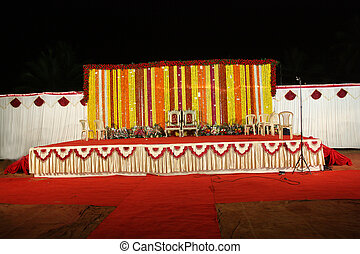 A view of an Indian wedding stage with traditional floral decoration.