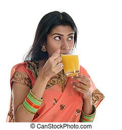 Indian woman drinking orange juice