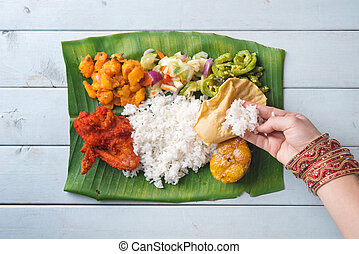Indian woman eating banana leaf rice