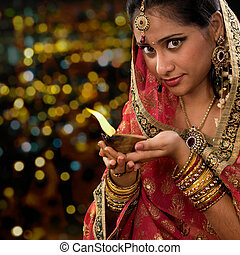 Indian woman hands holding diwali oil lamp
