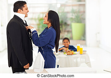 indian woman helping husband with tie