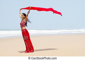 indian woman holding sari on windy beach