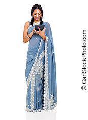 indian woman in saree using tablet computer