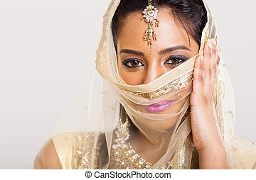 indian woman in sari costume covering her face