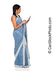 indian woman in sari using tablet computer