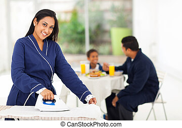 indian woman ironing while husband and son having breakfast