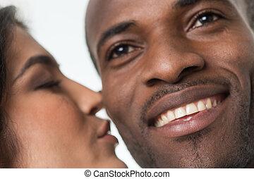 indian woman kissing black man on cheek. closeup portrait of...