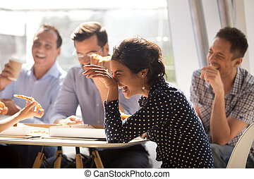 Indian woman laughing eating pizza with diverse coworkers in off
