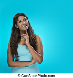 Indian Woman looking upwards on blue background. - Portrait...