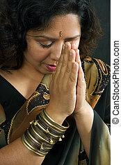 A beautiful Indian woman wearing a traditional sari and praying.