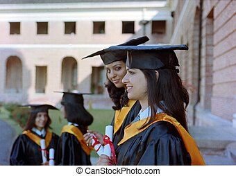 Indian Woman standing in a graduation group and smiling after convocation ceremony.