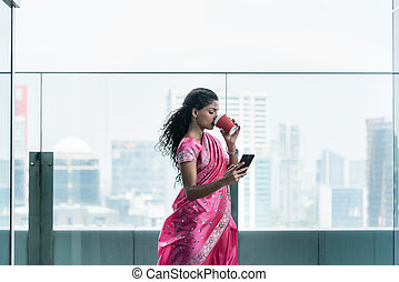 Indian young woman drinking coffee while using a mobile phone
