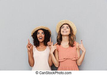 indicare, paglia, sopra, copyspace, mentre, isolato, ritratto, sorridente, donne, ragazze, dita, cappelli, felice, il portare, due, fondo, grigio, multiethnic, caucasico, americano, africano, verso l'alto