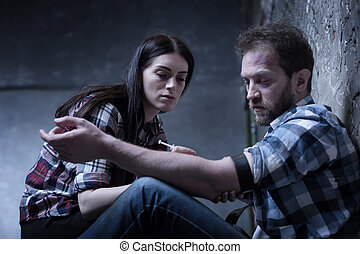 Indifferent drug addicted couple making heroin injection indoors