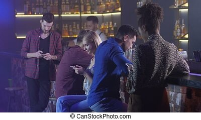 Indifferent friends using phones at bar counter - Mixed race...