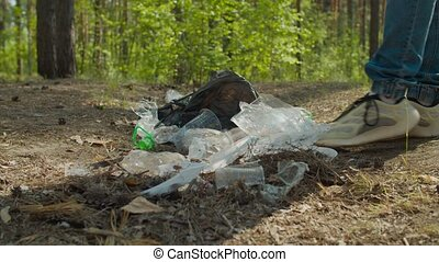 Close-up of indifferent man in sport shoes stepping over pile of plastic waste, scattered on forest floor. Disregard of environmental pollution and ecology problems.