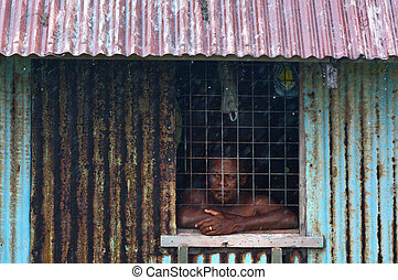 Fijian man looks out of the window during a Tropical Cyclone