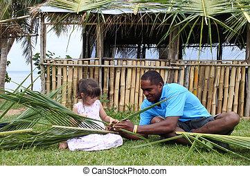 Indigenous Fijian man teach young tourist girl how to create...