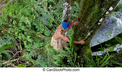 Indigenous Hunter Climbing A Tree In The Amazon Rainforest...