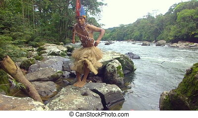 Indigenous Hunter Jumping On The Stones In The Amazon Rainforest