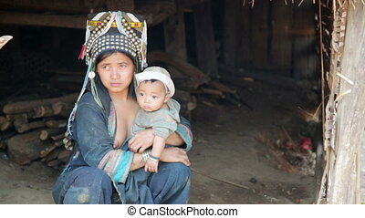 indigenous tribal native Akha woman carry baby in hill...