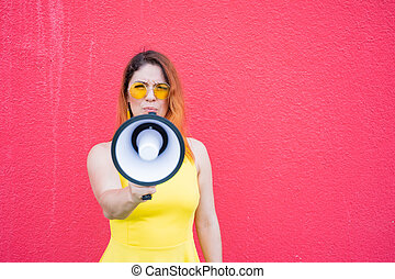 Indignant woman in sunglasses shouts into a megaphone on a ...